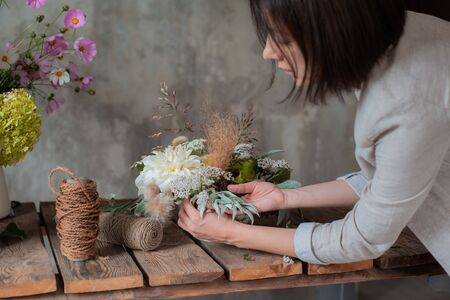 Female professional florist prepares the arrangement of wild flowers. Flower shop. Background concrete gray wall. Concept inspiration, floral, greetings, spring, ornament flowers. Stock Photo - 130128174