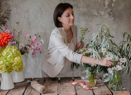 Female professional florist prepares the arrangement of wild flowers. Flower shop. Background concrete gray wall. Concept inspiration, floral, greetings, spring, ornament flowers. Stock Photo - 130128175