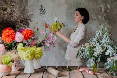 Female professional florist prepares the arrangement of wild flowers. Flower shop. Background concrete gray wall. Concept inspiration, floral, greetings, spring, ornament flowers. Stock Photo
