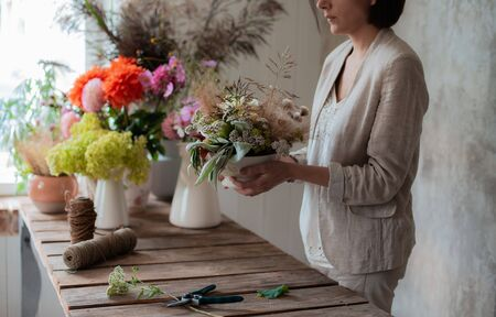Female professional florist prepares the arrangement of wild flowers. Flower shop. Background concrete gray wall. Concept inspiration, floral, greetings, spring, ornament flowers. Stock Photo - 130128179