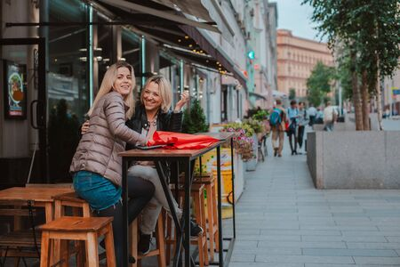 Two young women friends met in a city street cafe and have fun chatting. Friendly chance meeting in autumn