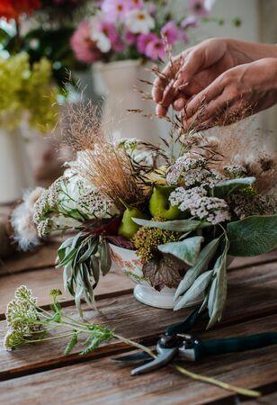 Female professional florist prepares the arrangement of wild flowers. Flower shop. Background concrete gray wall. Concept inspiration, floral, greetings, spring, ornament flowers.