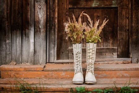 autumn bouquet in rubber boots on the background of old wooden doors and the village threshold. Free space for text. Autumn background.