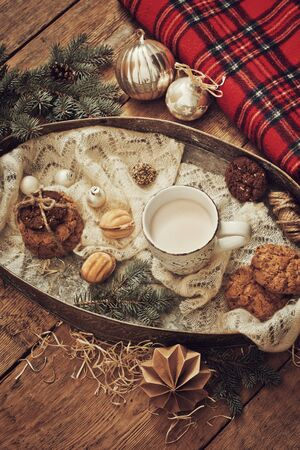 Mug with drink and cookies with Christmas decoration on wooden background