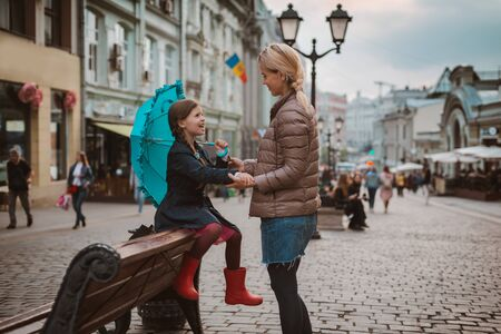 Little girl 6 years old child with an umbrella in rubber boots having fun with her mother on a bench center Moscow in the fall or spring. Autumn spring urban fashion. Family outing. 写真素材