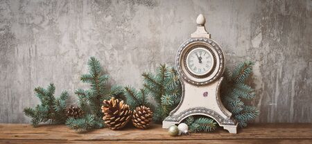Christmas tree branches with cones on a dark wooden Board against a gray concrete wall. Rustic new year decorations in retro style vintage antique clock. Copy space for text mockup Stock Photo