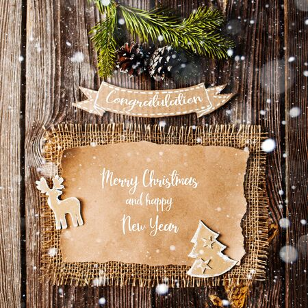 Christmas letter of congratulations in a rustic retro style of cardboard brown wooden background. Cheap new year with their hands. View from above. Flat lay. copy space and text
