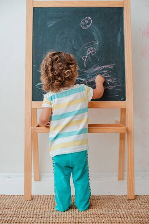 small child draws with chalk on a black chalk Board at home in the nursery against a gray wall. Childrens educational toys for fine motor skills and thinking. copy space for text. free space