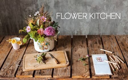 An ancient pot with a composition of flowers on a wooden rustic table against a concrete wall. concept of inspiration, greetings, spring, ornament flowers, floral kitchen, fashion, floristry, artist