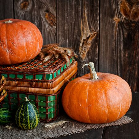 Happy Thanksgiving background, pumpkins and wicker basket on old wooden table. Halloween. the autumn festival concept for autumn, harvest