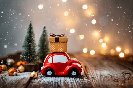 New year decoration and background for greetings with free space for text. Toy car carries a gift on the background of Christmas trees and lights bokeh on a wooden. 2020