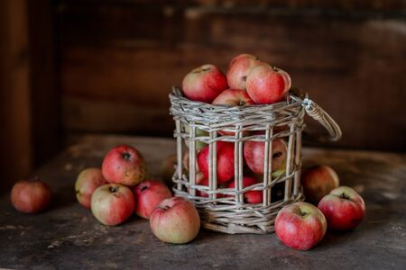 Fresh harvest of ripe and healthy farm apples in a glass jar, in a basket. Still life autumn rustic by the window and an old chest of drawers on a dark background.