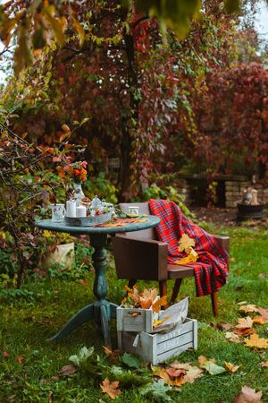 cozy patio. Autumn leaves lie on a wooden antique round table with crockery cups and cookies and candles. next to an old chair with colorful rug and wooden crates on the ground. autumn backyard dark Stock Photo