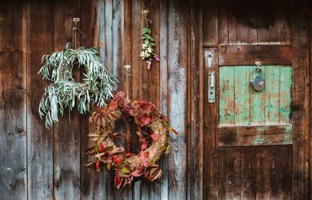 Fall front porch. autumn wreath and pumpkins on old wooden rustic background at doors. autumn composition and copy space for text