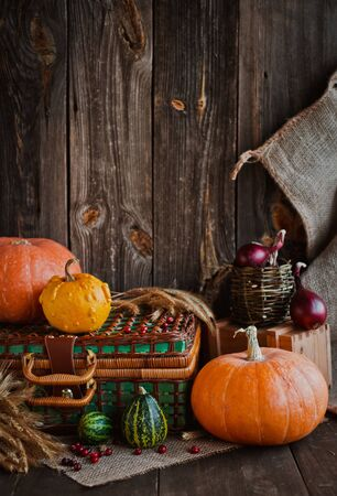 Happy Thanksgiving background, pumpkins and wicker basket on old wooden table. Halloween. the autumn festival concept for autumn, harvest. vertical