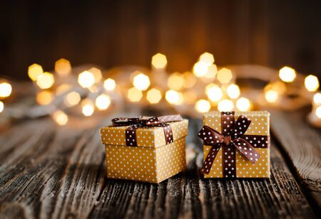 Christmas gift box lay on a wooden table on a background bokeh of festive lights. New year background for congratulations. Copy space for text and mockup Stock Photo