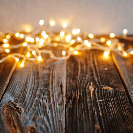 Empty old wooden countertop with blurred gold bokeh Christmas lights abstract background. For mounting product display or layout design