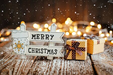 New year decoration and background for greetings with free space for text. Inscription with congratulations on the background of Christmas trees and lights bokeh on a wooden. 2020