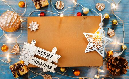 New year decorations around Christmas letter empty space for text burning lights garlands on blue wooden background. View from above. Flat lay. copy space Brown rustic style
