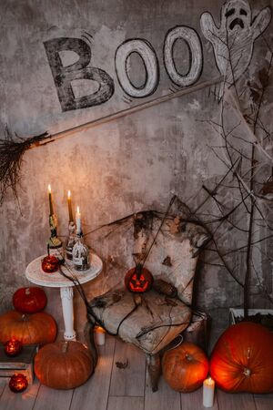 Background decorations for Halloween celebration. A scary composition with Jacks pumpkin and burning candles, spider webs witchs broom with painted Ghost concrete wall. witchcraft, mysticism Stock Photo