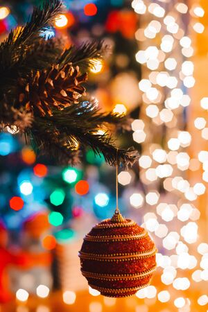 Christmas ball hangs on a decorated fir tree against the background of burning bokeh lights at night. Happy new year greeting card concept