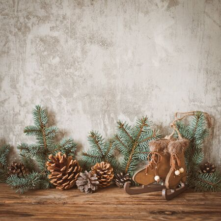 Christmas tree branches with cones on a dark wooden Board against a gray concrete wall. Rustic new year decorations in retro style. Copy space for text mockup Stock Photo