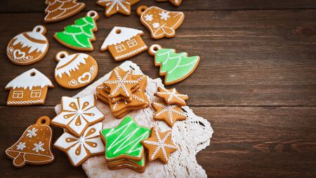 festive Christmas gingerbread cookies in the shape of a star lie on a wooden dark brown background. top view with copy space background new year