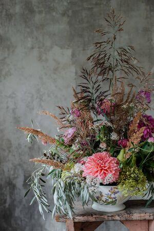 large floral arrangement bouquet on the desktop florist on the background of a concrete wall. The concept of inspiration, congratulations, spring, flower decoration.