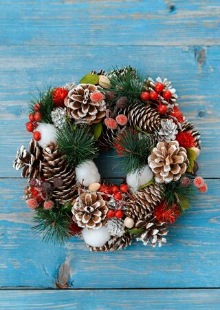 Christmas wreath with cones on a blue wooden Board. Rustic new year decorations in retro style. Copy space for text layout. top view with copy space