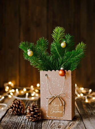 Christmas composition. Paper bag with and bumps fir branches on brown wooden background and bokeh lights. Christmas, winter, new year concept. mockup free space