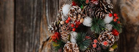 Christmas wreath of spruce and Christmas tree decorations with lights and snow on the old textured wooden background. free space, mock-up
