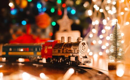 toy vintage steam locomotive on the floor under a decorated Christmas tree on a background of bokeh lights garland. Christmas and New year celebration concept, background. free space Stock Photo