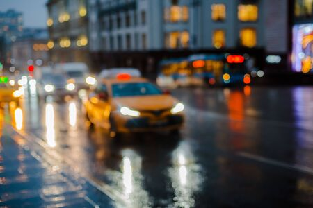 Wet night city street rain Bokeh reflection bright colorful lights puddles sidewalk. Car headlights lighting reflection wet asphalt road Defocused selective focus fuzzy background with red lights