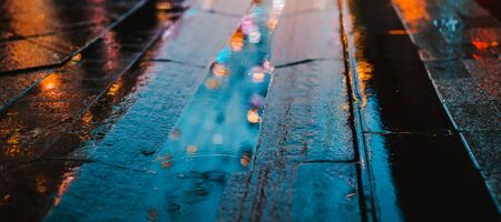 Rainy night in a big city, reflection of colorful city lights on the wet road surface. The view from the street level feet of pedestrians. abstract background. defocused, depth of field, bokeh