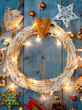 New year decorations around Christmas wreath burning lights garlands on blue wooden background. View from above. Flat lay. copy space Stock Photo