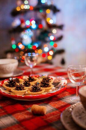 Traditionally decorated Christmas table. Creative decoration of the festive table cones on a plate on the background of bokeh lights. The concept of celebrating the new year