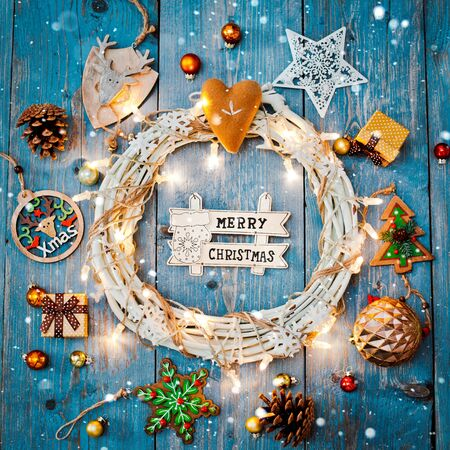 Christmas white wreath tree wooden decoration skates around Christmas letter empty space text burning lights garland classic blue wooden background. view from the top. copy space brown rustic style
