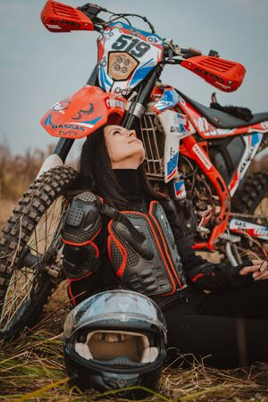 Beautiful brunette woman in motorcycle outfit. Female motocross racer next to her motorcycle. Russia Moscow 20 October 2019