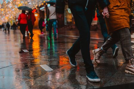 Rainy night in a big city, reflection of colorful city lights on the wet road surface. The view from the street level feet of pedestrians. abstract background. defocused, depth of field, bokeh Stock fotó