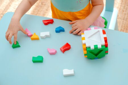 close-up of the childs hands collect puzzle sorter. Cube with inserted geometric shapes and colored plastic blocks. Educational childrens game toy Фото со стока
