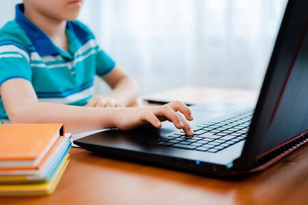 Distance learning online education. A schoolboy boy studies at home and does school homework. A home distance learning. Фото со стока