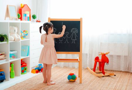 A girl stands in the childrens room with a blackboard and draws a family with chalk. concept of family, education, entertainment, games at home, in kindergarten