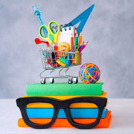 Colorful school supplies shopping basket gray background with a copy text space. A stack of books with colorful covers frame glasses. The concept of returning to school for new academic year.