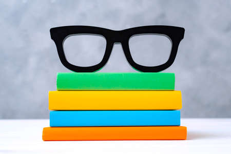 stack of colorful books with glasses on a white wooden table against a gray wall. The concept of going back to school, reading, library, literature, study, education.