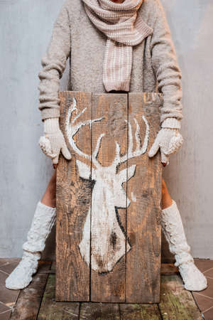 woman dressed for winter with white knitted fashion items holds a wooden poster with painted white deer gray background. concept onset of winter holidays and congratulations on new year and Christmas. Stok Fotoğraf