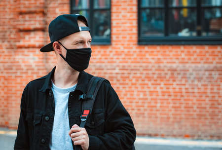 young fashionable man youth casual wear protective black mask walks through urban city sunset. trendy teen guy walks around city coronavirus pandemic. Spring. Modern Fashion 2020.