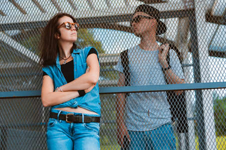 young stylish pair hipsters sunglasses, guy girl urban space separated cage fence. concept relationship between man woman, disagreements, misunderstandings conflict, depression, different sides