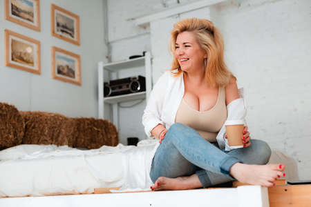 beautiful plus-size girl with big breasts sits on a white floor with coffee. Body positive, diet, curvy figure, sexy, blonde 30 years old, fashion, gluttony, care.