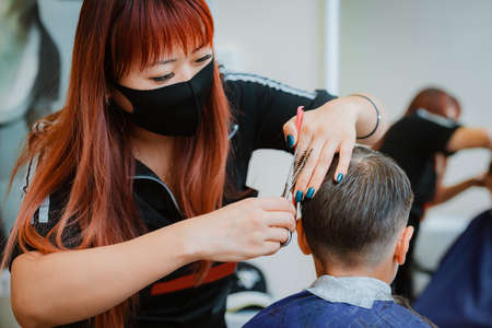 Haircut the child to the client with safety measures. asian hair stylist.