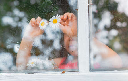 Raindrops on the glass of a village window, chamomile flowers eyes in childrens hands look at the rain. Happy childhood and holidays in the country. The background of the summer weather.